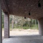 Skärmtaket inifrån. Byggnaden ligger i skydd av skogen och omges av naturmark.